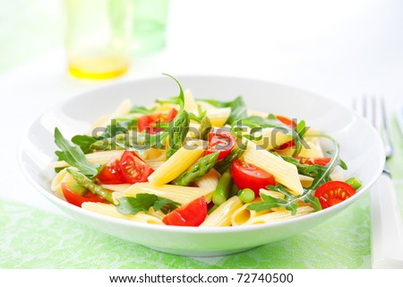 Pasta penne with asparagus,tomato and rucola in bowl