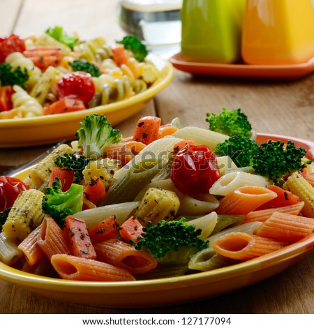 Pasta penne with broccoli, carrot, corn, and tomatoes on the kitchen table