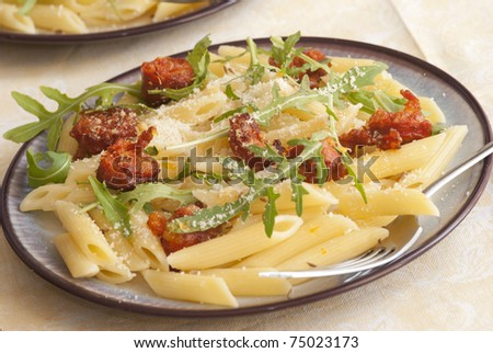 Pasta Penne with chorizo sausages, rocket and cheese on a plate