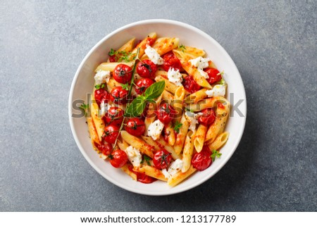 Pasta penne with roasted tomato, sauce, mozzarella cheese. Grey stone background. Top view. ストックフォト ©