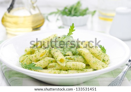 pasta penne with sauce of arugula and green peas on a plate close-up