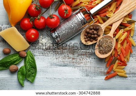 Shutterstock Pasta penne with tomatoes, cheese and basil on color wooden  background