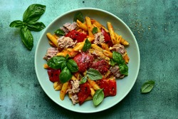 Pasta penne with tuna and vegetables in tomato sauce in a bowl over green slate, stone or concrete background. Topview with copy space.
