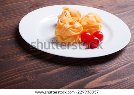 pasta raw three circles and three cherry tomatoes on a white plate on brown wooden table top view