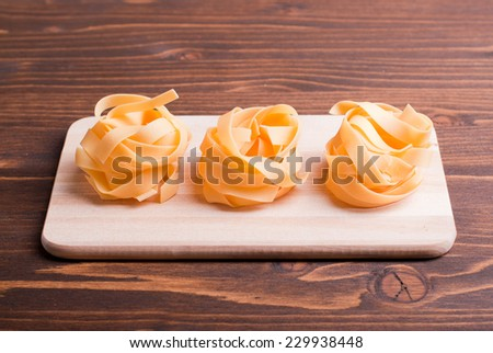 pasta raw three circles in a row on a small cutting board on a light table korrichenvom side view