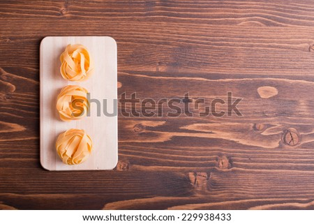 pasta raw three circles in a row on a small light on a cutting board korrichenvom table top view on the right place for text