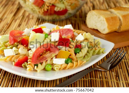 Pasta salad with fresh vegetables (tomato, pea, bell pepper, cucumber ...