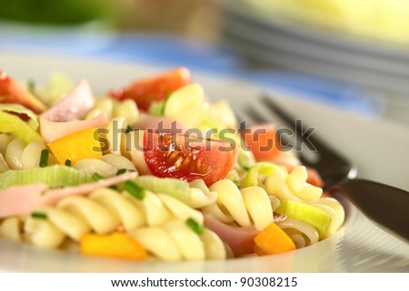 Pasta salad with leek, cherry tomato, yellow bell pepper and ham garnished with chives (Selective Focus, Focus on the tomato in the front)