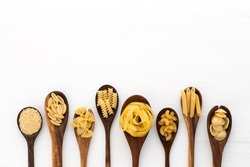 Pasta selection of penne, gnocci, rigatoni, casarecce, fiorelli, pasta Farfalle, pasta A Riso, Orecchiette Pugliesi, Gnocco Sardo and Farfalle in wooden spoons over white background