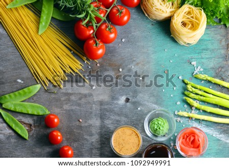 Pasta. Several kinds of dry pasta with vegetables and herbs. Tomatoes, greens, asparagus on a wooden table. Free space for text. View from above #1092949991