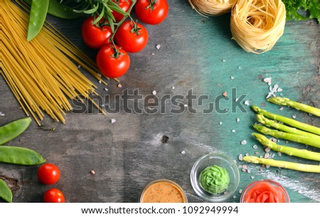 Pasta. Several kinds of dry pasta with vegetables and herbs. Tomatoes, greens, asparagus on a wooden table. Free space for text. View from above #1092949994