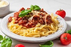 Pasta spaghetti bolognese with minced beef sauce, tomatoes, parmesan cheese and fresh basil in a plate on white table. Italian food
