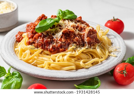 Pasta spaghetti bolognese with minced beef sauce, tomatoes, parmesan cheese and fresh basil in a plate on white table. Italian food Foto d'archivio ©