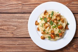 Pasta spaghetti with chanterelles mushrooms on a wooden background top view