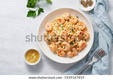 Pasta spaghetti with grilled shrimps bechamel sauce. Spaghetti with seafood rich cream. Cooking mediterranean food with savory prawns, copy space top view, blue table, italian cuisine