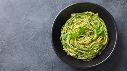 Pasta spaghetti with pesto sauce and fresh basil leaves in black bowl. Grey background. Copy space. Top view.