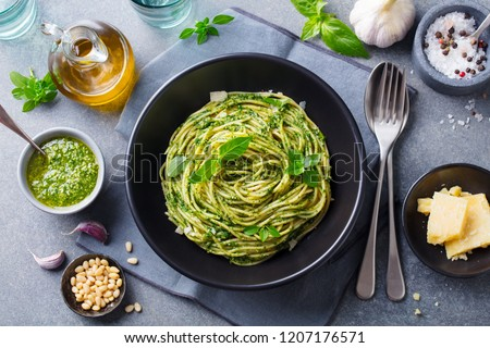 Pasta spaghetti with pesto sauce and fresh basil leaves in black bowl. Grey background. Top view. Zdjęcia stock ©