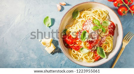 Pasta spaghetti with tomato sauce and cheese parmesan served on plate on blue table background. Top View with copy space.
