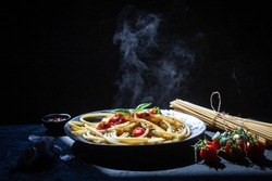 Pasta, spaghetti with tomato sauce in black bowl. Grey stone background., on dark Background with smoke and steam, view. Selective Focus at the front.hot food