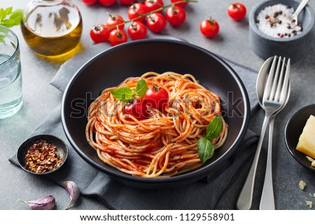 Stock Photo Pasta, spaghetti with tomato sauce in black bowl on grey background.