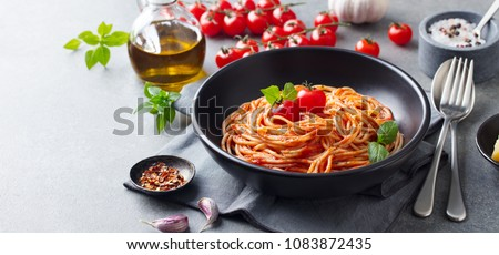 Pasta, spaghetti with tomato sauce in black bowl on grey background. Copy space.