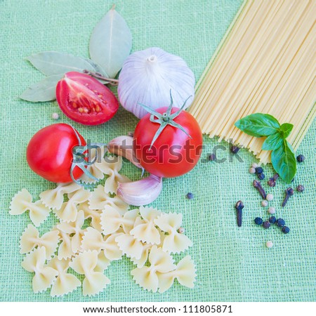 Pasta, spices and vegetables on a green textile background