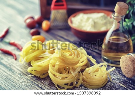 Pasta uncooked on the table. Noodles in the form of nests. Flour and seasonings.