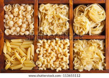 Pasta variety in wooden compartment box - top view