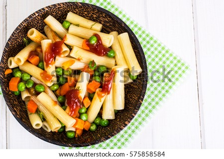 Pasta with carrots and green peas in wooden bowl. Studio Photo #575858584