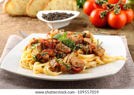 Pasta with chunks of fresh tuna, tomato and mint on complex background - stock photo
