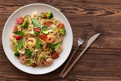 Pasta with fried shrimps, cherry tomatoes, zucchini, broccoli and basil. Top view.