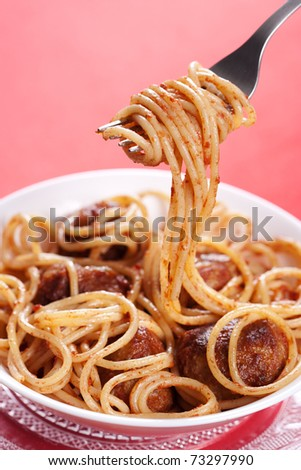 Pasta with meatballs and tomato sauce on red background