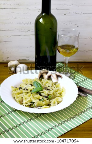 pasta with mushrooms and pesto, with white wine in the background