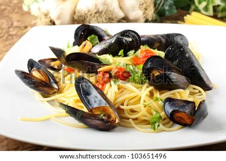 Pasta with mussels and cherry tomatoes on complex background - stock photo