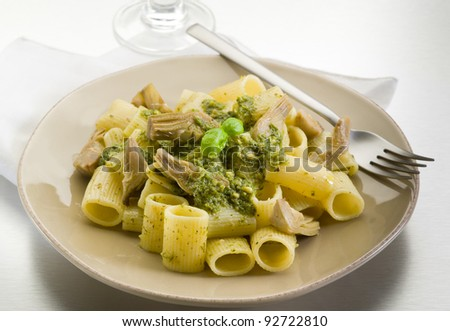 pasta with pesto and artichoke over steel background
