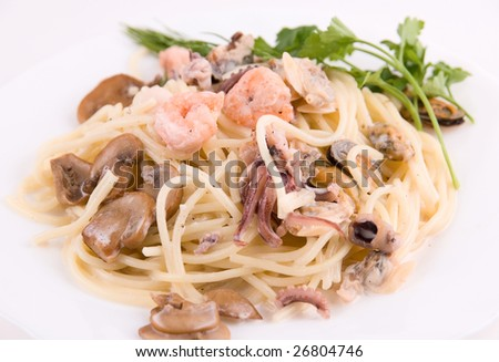 Pasta with seafood and mushrooms on white plate