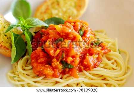 pasta with tomato sauce and meat and garlic bread - stock photo