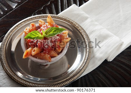 Pasta with tomato sauce in a very small bowl. Shallow depth of field