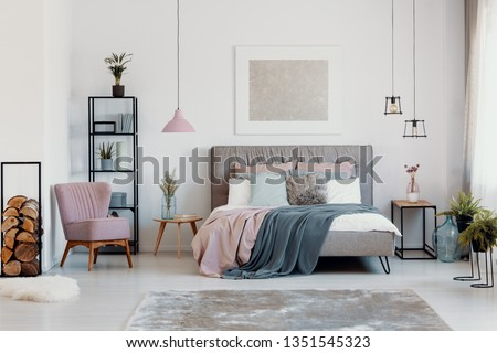 Paste pink armchair and lamp in elegant bedroom interior with comfortable bed with pillows, blanket and duvet, warm carpet on floor