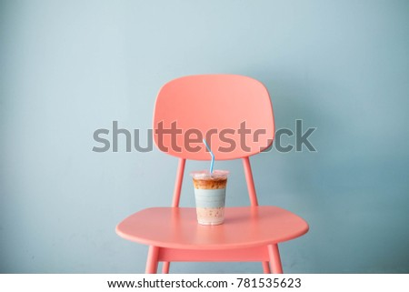 Pastel and minimal concept : A clear plastic cup of ice coffee latte with pastel blue straw on pastel pink table on pastel blue background, close up, copy space #781535623