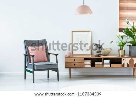 Pastel armchair next to a wooden cupboard with poster and plant in living room interior