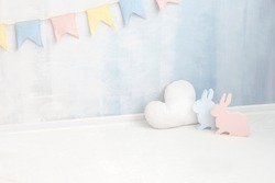 Pastel baby background in soft light blue and pink colors with rabbit bunny cloud figure near paint wall in child room. Easter newborn concept greeting card