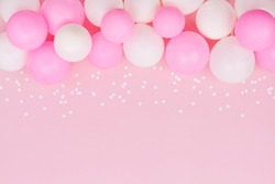 Pastel balloons and white confetti on pink background top view. Flat lay style.