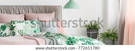 Pastel bed with headboard, decorative cushions and botanic patterned bedding next to window