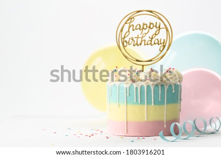 Photo of  Pastel birthday cake with drip icing and balloons