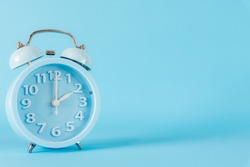 Pastel blue alarm clock with two o'clock on blue background. 2 am, 2 pm. Time concept.