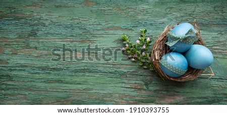 Pastel blue colored easter eggs on green shabby wood. Country style easter decoration with flowers. Background for easter greetings with space for text. Top view photography. Foto stock ©