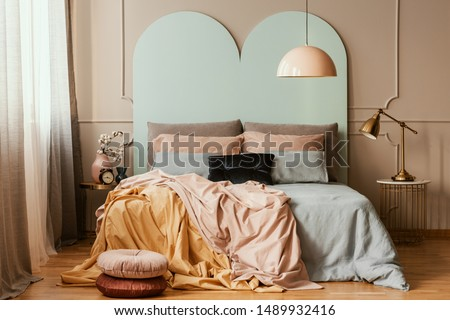 Pastel blue, pink and orange bedding on double bed in chic bedroom interior