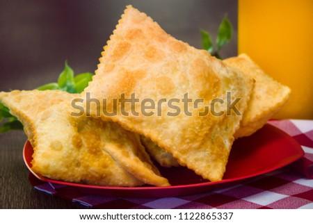 Pastel, Brazilian snack served on a wooden table accompanied by orange juice. Brazilian food #1122865337