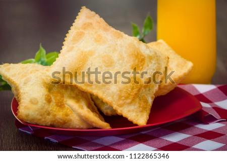 Pastel, Brazilian snack served on a wooden table accompanied by orange juice. Brazilian food #1122865346
